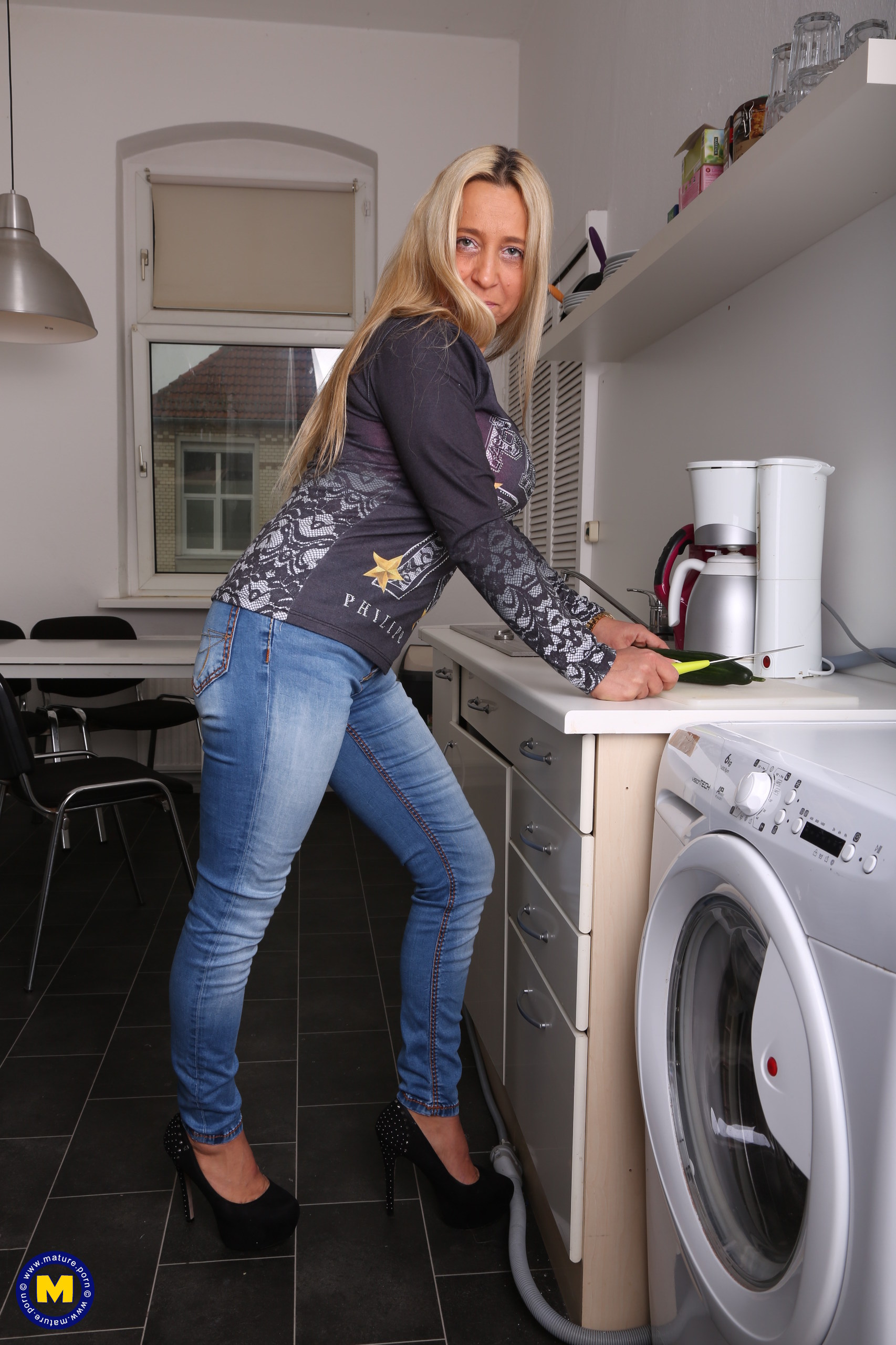 Naughty German mom toying in her kitchen with her cucumber